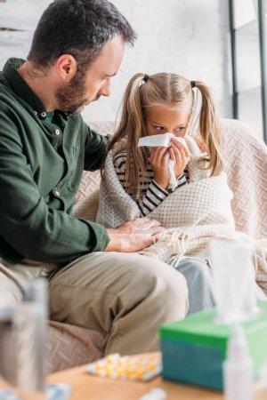 Photo pour Foyer sélectif de l'homme assis près de fille malade éternuer dans la serviette - image libre de droit
