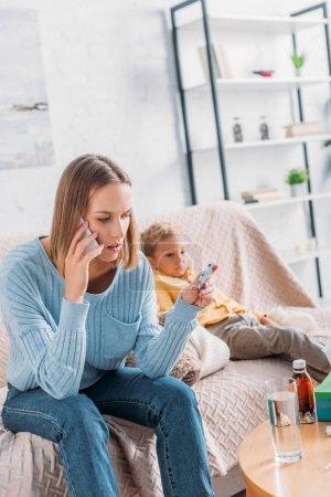 Foto de Mujer preocupada sosteniendo ampolla de píldoras y hablando en el teléfono inteligente mientras está sentado cerca de hijo enfermo - Imagen libre de derechos