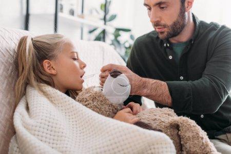 Aufmerksamer Vater gibt kranker Tochter mit Teddybär Medikamente