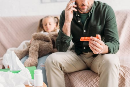 cropped view of man talking on smartphone and holding blister of pills while sitting near sick daughter