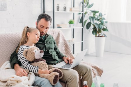 Photo for Upset, diseased child holding teddy bear while sitting on sofa near father - Royalty Free Image