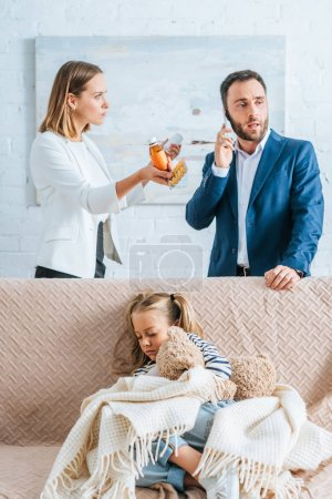 Photo for Worried mother holding medicines and father talking on smartphone near diseased daughter sitting on sofa under blanket - Royalty Free Image