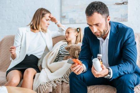 Photo pour Père inquiet tenant des médicaments et mère assise près de sa fille malade - image libre de droit