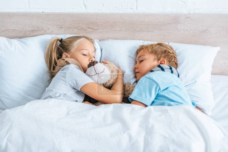 Photo for Diseased brother and sister sleeping in bed with teddy bear - Royalty Free Image