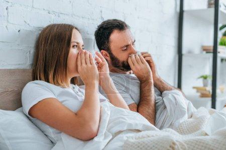 Photo pour Mari malade et femme éternuer tout en étant couché ensemble - image libre de droit