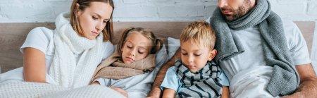 Foto de Foto panorámica de la familia enferma en pañuelos cálidos en la cama debajo de mantas. - Imagen libre de derechos