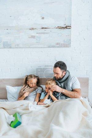 Photo pour Homme malade et les enfants dans des foulards chauds couchés dans le lit sous la couverture - image libre de droit