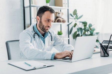 Photo pour Médecin positif assis sur le lieu de travail et utilisant un ordinateur portable - image libre de droit