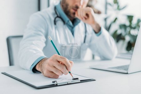 Photo for Partial view of doctor writing prescription on clipboard - Royalty Free Image