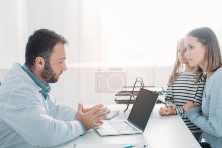 poważny lekarz rozmawiając z matką i córką podczas siedzenia przy stole