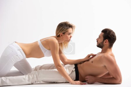 Photo for Beautiful seductive couple of lovers lying on white - Royalty Free Image