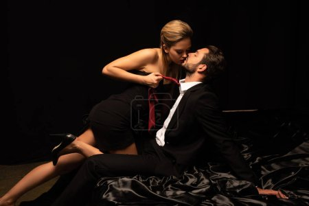 Photo for Elegant couple of lovers playing with tie on bed in dark room - Royalty Free Image