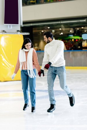Photo for Cheerful young couple holding hands and skating on rink - Royalty Free Image