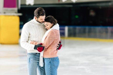 Photo pour Jeune couple en chandails étreignant sur la patinoire - image libre de droit