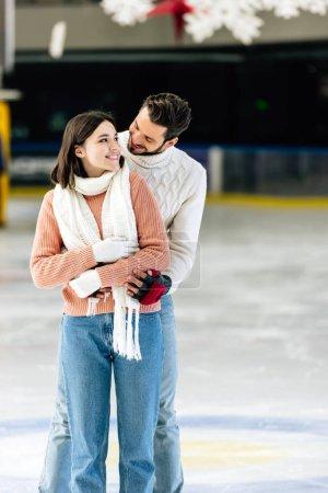 Foto de Feliz joven pareja en suéteres abrazándose en pista de patinaje - Imagen libre de derechos