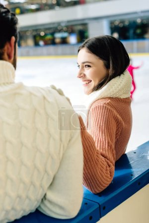 young smiling couple in sweaters spending time on skating rink