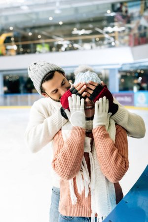 Photo pour Homme joyeux fermant les yeux à la femme pour faire une surprise sur la patinoire - image libre de droit