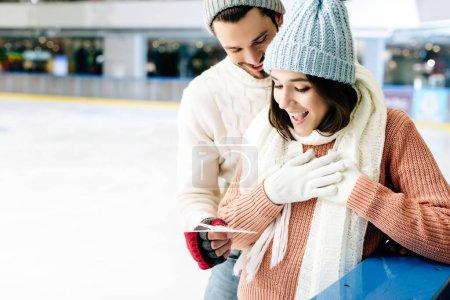 Foto de El hombre feliz dando carta de felicitación el día de la noche a la mujer emocionada en la pista de patinaje. - Imagen libre de derechos