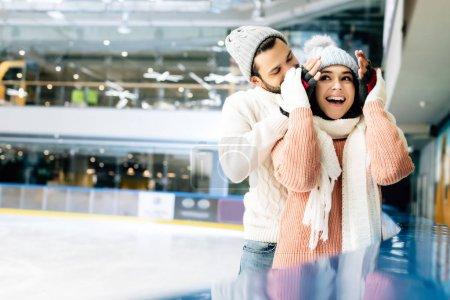 Photo pour Homme joyeux fermer les yeux à femme excitée pour faire une surprise sur la patinoire - image libre de droit