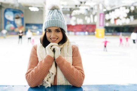 Photo for Smiling girl in sweater, scarf, gloves and hat standing on skating rink - Royalty Free Image
