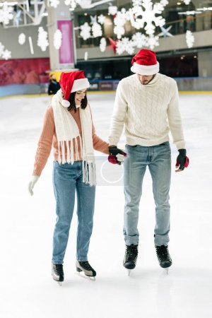 Photo for Happy couple in santa hats holding hands while skating on rink - Royalty Free Image