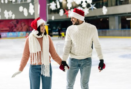 Photo pour Beau couple heureux dans santa chapeaux tenant la main au moment de Noël sur patinoire - image libre de droit