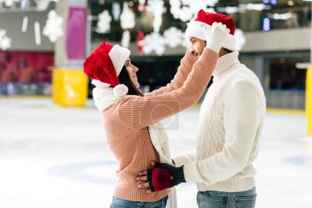 Photo for Cheerful couple in santa hats spending christmastime on skating rink - Royalty Free Image