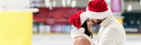 Photo for Panoramic shot of beautiful happy couple in santa hats spending christmastime on skating rink - Royalty Free Image