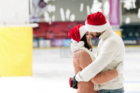 Photo for Beautiful couple in santa hats spending time on skating rink - Royalty Free Image