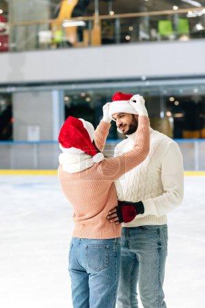 Photo pour Beau couple heureux en santa chapeaux passer du temps sur la patinoire - image libre de droit