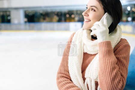 Photo for Attractive smiling girl talking on smartphone on skating rink - Royalty Free Image