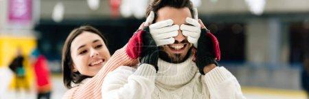 Photo pour Photo panoramique d'une belle femme fermant les yeux à un homme souriant pour faire une surprise sur la patinoire - image libre de droit