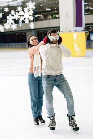 Photo pour Femme joyeuse fermant les yeux à l'homme pour faire une surprise sur la patinoire - image libre de droit