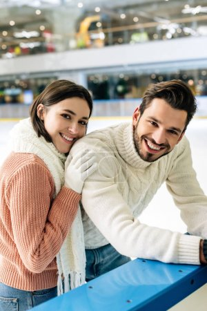Photo for Young couple in sweaters spending time on skating rink - Royalty Free Image