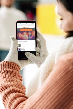 Photo pour Kyiv, Ukraine - November 15, 2019 : cropped view of woman in gloves holding smartphone with soundcloud app on screen - image libre de droit