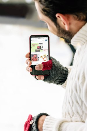 Photo for KYIV, UKRAINE - NOVEMBER 15, 2019: cropped view of man in gloves holding smartphone with ebay app on screen, on skating rink - Royalty Free Image