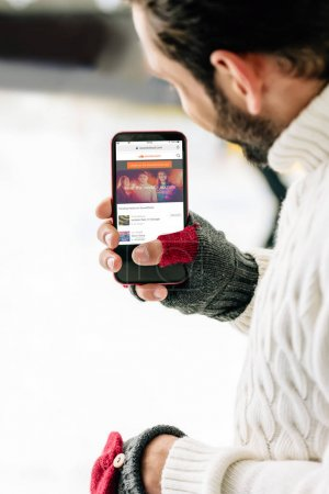 KYIV, UKRAINE - NOVEMBER 15, 2019: cropped view of man in gloves holding smartphone with soundcloud app on screen, on skating rink
