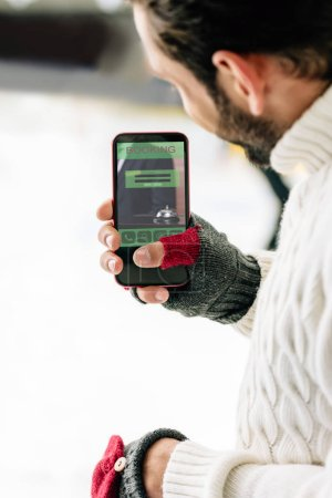 Photo for KYIV, UKRAINE - NOVEMBER 15, 2019: cropped view of man in gloves holding smartphone with booking app on screen, on skating rink - Royalty Free Image