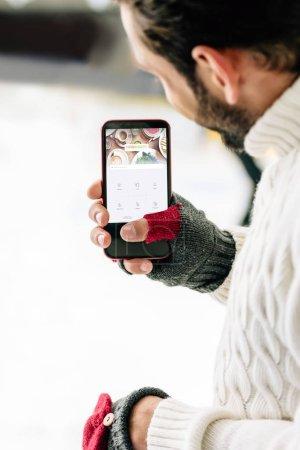 Photo pour KYIV, UKRAINE - 15 NOVEMBRE 2019 : vue recadrée de l'homme en gants tenant un smartphone avec une application quadratique à l'écran, sur une patinoire - image libre de droit