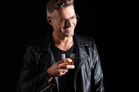 Hombre sonriente en chaqueta de cuero y gafas de sol sosteniendo vaso de whisky aislado en negro