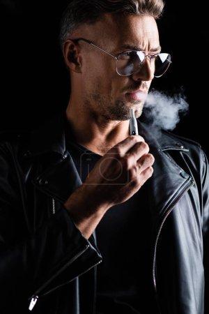 Photo pour KYIV, UKRAINE - 11 OCTOBRE 2019 : Beau homme en veste en cuir fumant iqos isolé sur noir - image libre de droit