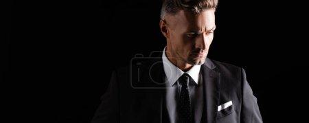 Foto de Foto panorámica de un empresario guapo que mira hacia otro aislado en negro - Imagen libre de derechos
