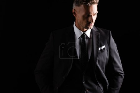 Photo pour Un homme d'affaires sérieux regardant ailleurs isolé sur le noir - image libre de droit