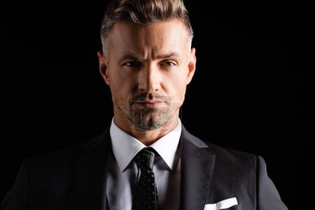 Photo pour Homme d'affaires confiant en tenue formelle regardant la caméra isolée sur noir - image libre de droit