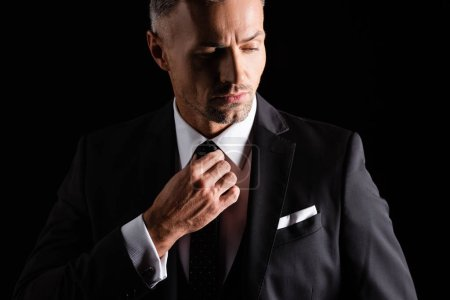 Photo for Handsome businessman adjusting tie while looking away isolated on black - Royalty Free Image