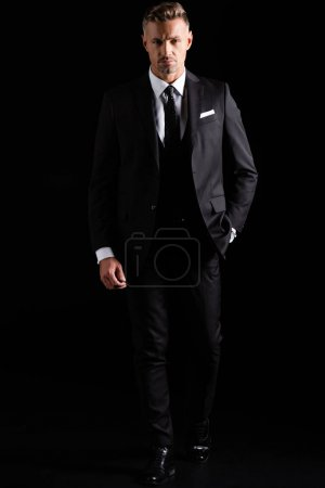 Photo for Full length of handsome businessman looking at camera isolated on black - Royalty Free Image