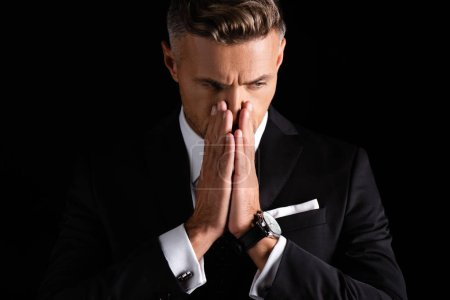 Photo pour Homme d'affaires pensif avec les mains par le visage regardant loin isolé sur noir - image libre de droit