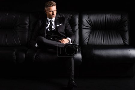 Photo for Confident businessman in formal wear sitting on couch isolated on black - Royalty Free Image