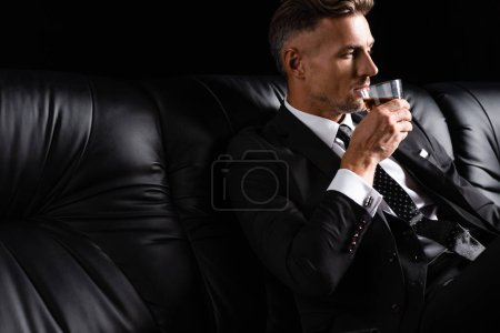 Handsome businessman drinking whiskey while sitting on couch isolated on black