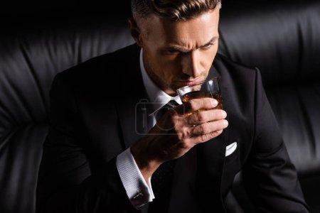 Photo pour Homme d'affaires buvant du whisky sur canapé isolé sur noir - image libre de droit